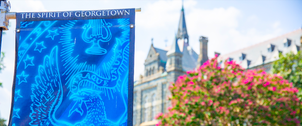 """Landscape image of blue Georgetown banner displaying the words """"The Spirit of Georgetown"""" at the top and the GU seal underneath. In the background is the facade of Healy Hall with pink flower bush in the foreground."""